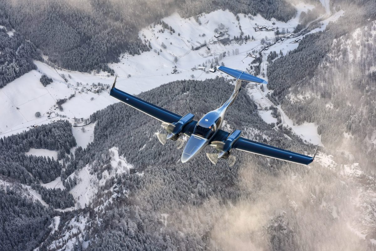 Diamond DA42 flying over alpine scenery
